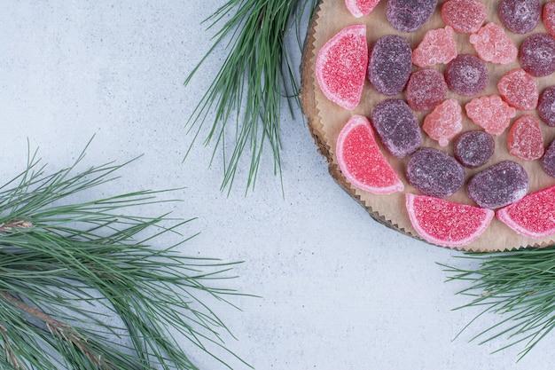 Разнообразие мармеладных конфет на деревянной доске.