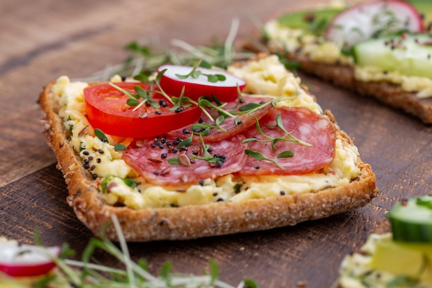 Разнообразные мини-бутерброды со сливочным сыром, овощами и салями. бутерброды с огурцом, редисом, помидорами, салями на сером фоне, вид сверху. плоская планировка.