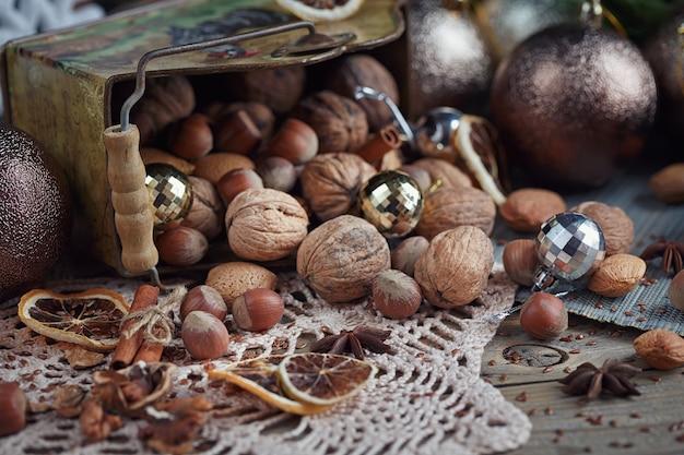 クリスマスと新年の装飾のナッツの様々な。モミの木の枝、キャンドル、休日が木製の背景に照らしてクリスマスと新年の構成