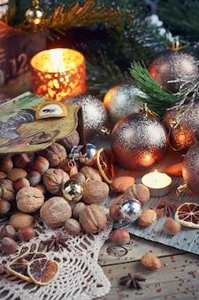 Разнообразие орехов в рождественских и новогодних украшениях. рождественская и новогодняя композиция с еловыми ветками, свечами и праздничным светом на деревянном фоне