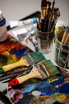 さまざまな絵筆と絵の具を使ったパレットで、アーティストの職場でプロの絵を描くことができます