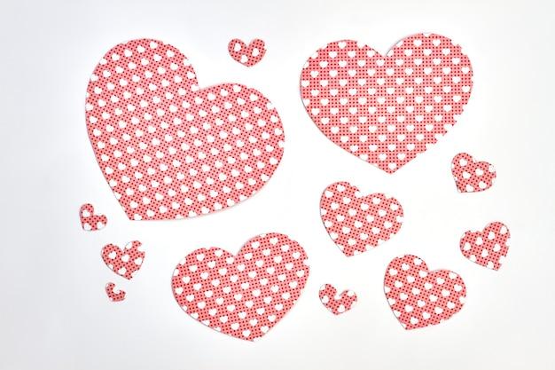 白い背景の上の紙の心の様々な。ハートが描かれた紙のハート。バレンタインの休日のロマンチックなデザイン。