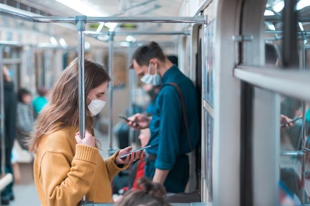 さまざまな乗客が地下鉄の車に乗ります。市内のコロナウイルス
