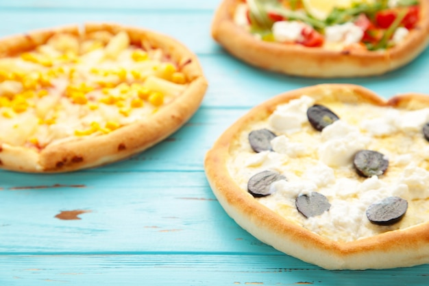 青い木製の背景にさまざまなピザ