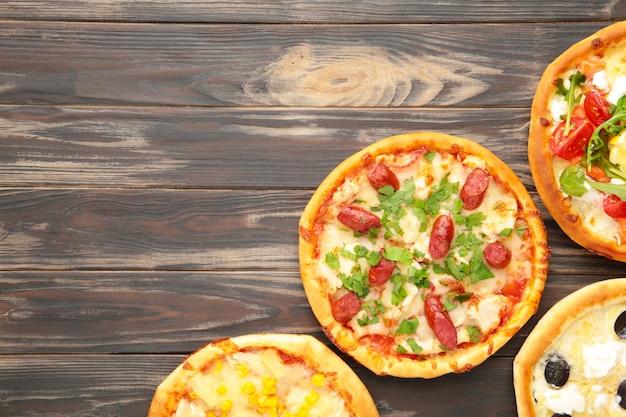茶色の木製の背景にさまざまなピザ