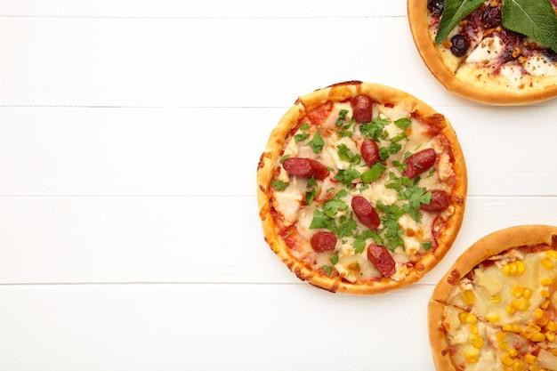 コピースペースを持つ白い木製の背景にさまざまなピザ