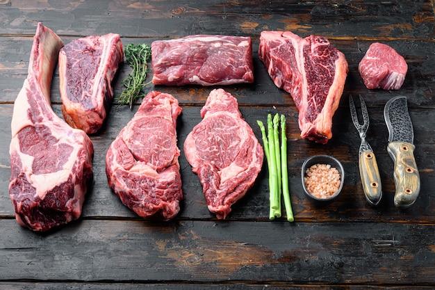 Разнообразные стейки из сырого говяжьего мяса для гриля с набором приправ и посуды