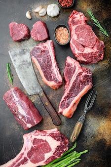 Разнообразие стейков из сырого говяжьего мяса для гриля с набором приправ и посуды