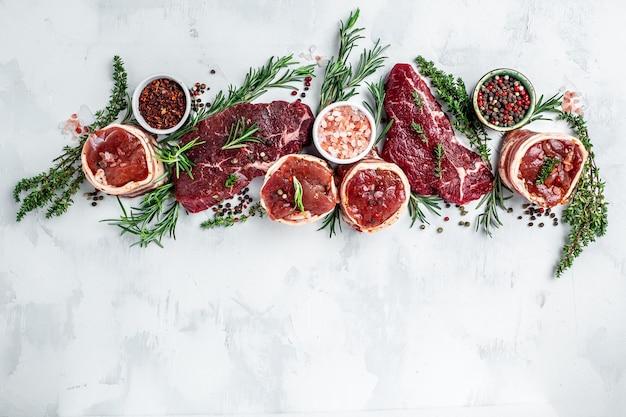 Разнообразие стейков сырого говяжьего мяса для гриля с приправами на светлом фоне. баннер, меню рецепт вид сверху.