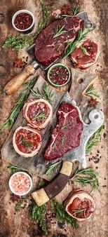 Разнообразие стейков из сырого говяжьего мяса для гриля с приправами над мясным ножом. баннер, меню рецепт вид сверху. вертикальное изображение.