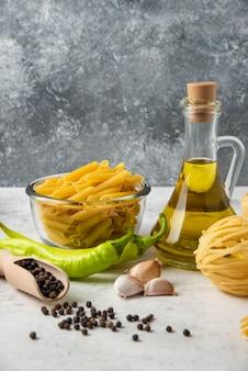 白いテーブルの上にさまざまな生パスタ、オリーブオイルのボトル、コショウの穀物と野菜。