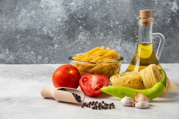 Разнообразие сырых макарон, бутылки оливкового масла, зерен перца и овощей на белом столе.