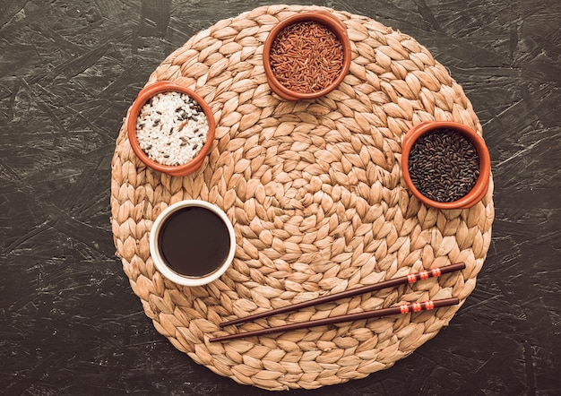 Разнообразие рисовых зерен в трех чашах над круговой тарелкой с палочками для еды