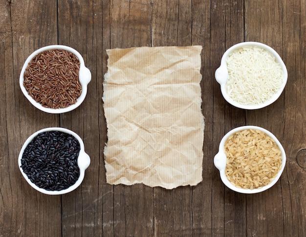 Разнообразие риса в мисках вокруг старой бумаги на деревянный стол сверху