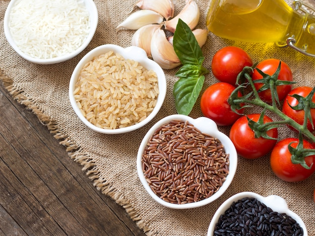 Разнообразие риса в мисках на деревянном столе крупным планом с копией пространства