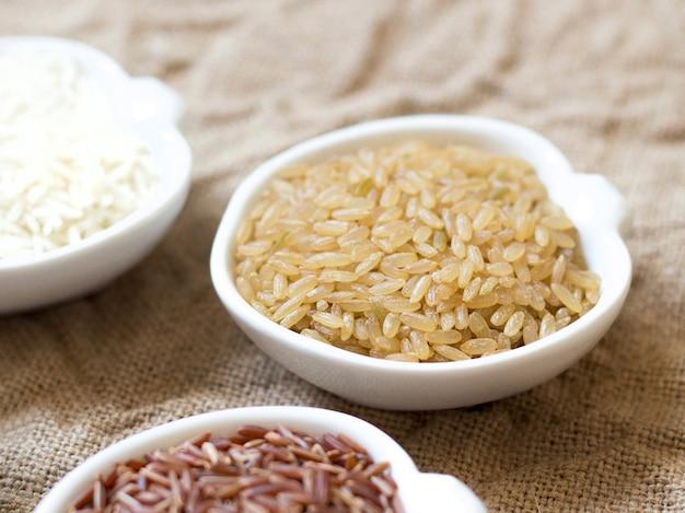 Разнообразие риса в мисках на деревянном столе крупным планом