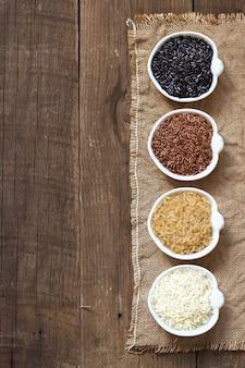 Разнообразие риса в мисках на деревянный стол сверху с копией пространства