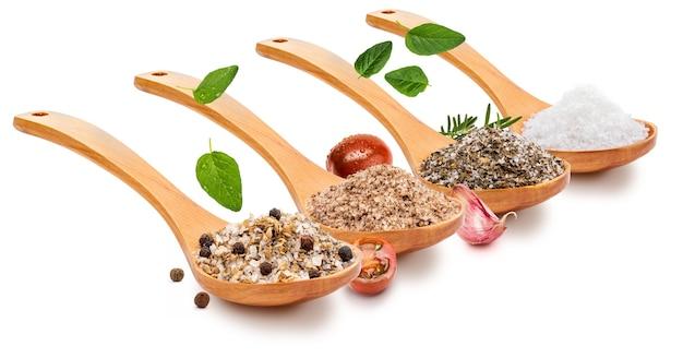 木のスプーンにさまざまなスパイス(トマト、ニンニク、オレガノ、ローズマリー、黒胡椒)を入れたさまざまな塩(塩)(さまざまな塩のコレクション)
