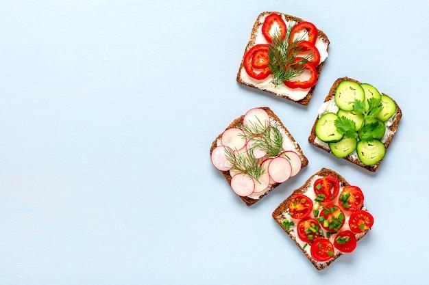 Разнообразие бутербродов на завтрак на синем столе