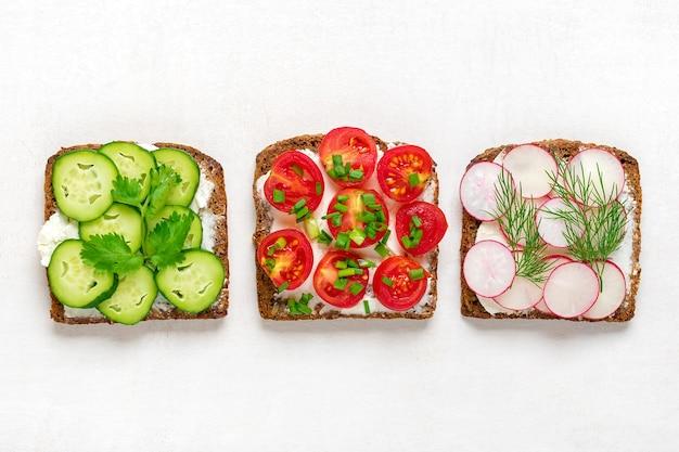 全粒粉の暗いパンのスライスと朝食のためのさまざまなサンドイッチ