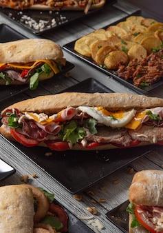 木製のテーブルの上のサンドイッチの様々な。アラカルトレストラン。地中海料理