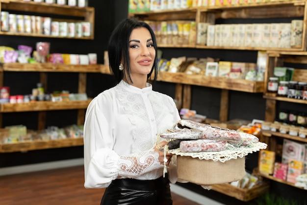 美しい女性の売り手の手にある素朴なトレイにさまざまなソーセージ製品のクローズアップ。