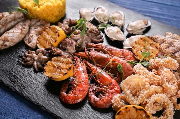 Разнообразие морепродуктов с рисом на грифельной тарелке