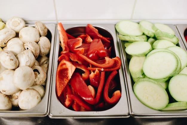 キノコ、ピーマン、ズッキーニなど、プロのキッチンで調理するために準備されたさまざまなスライス野菜