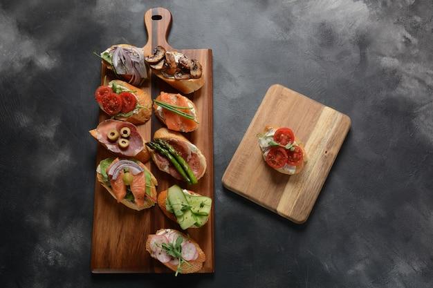 Разнообразие небольших бутербродов на деревянной доске