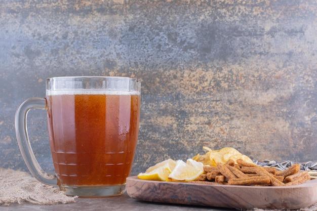 Разнообразие закусок и бокал пива на мраморном столе. фото высокого качества