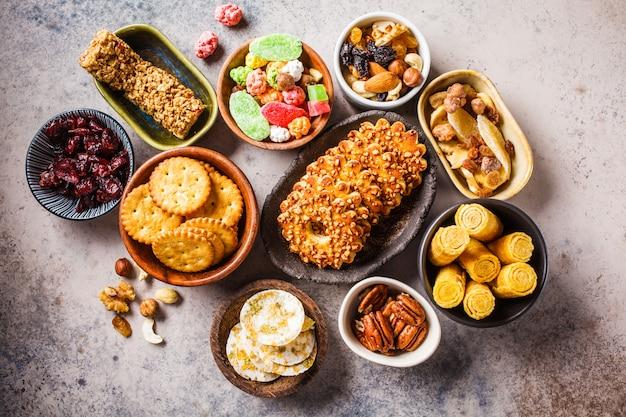 Разнообразие закусок и сладостей на сером фоне. вафли, орехи, сладости, печенье, чипсы и фрукты, вид сверху, плоская планировка.