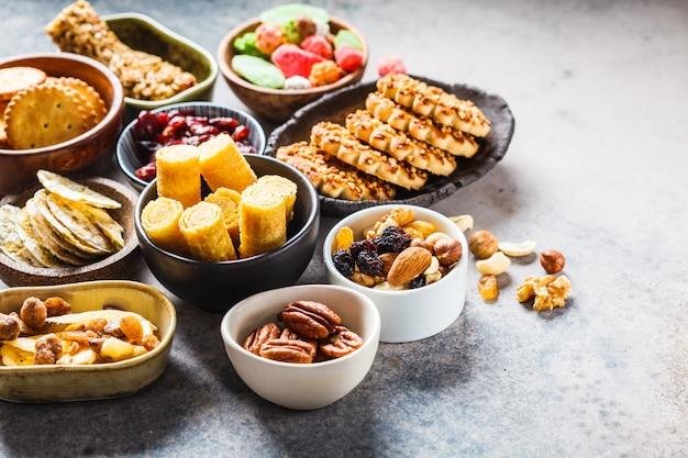 Разнообразие закусок и сладостей на сером фоне. вафли, орехи, сладости, печенье, чипсы и фрукты.