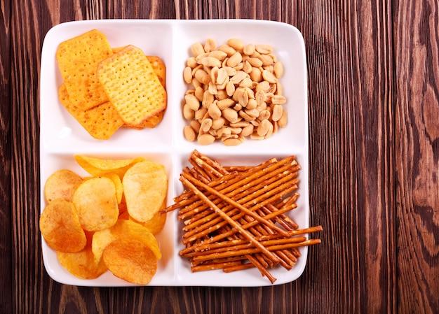 Разнообразие закусок на тарелку над деревянным столом
