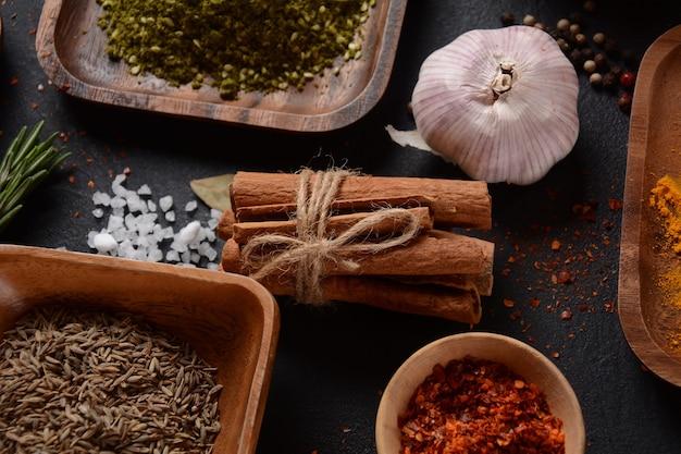台所のテーブルにさまざまなスパイスやハーブ。唐辛子粉、オレガノ、シナモンスティック、塩、にんにく