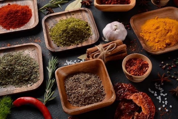 台所のテーブルにさまざまなスパイスやハーブ。暗い背景で調理するためのカラフルなさまざまなハーブやスパイス