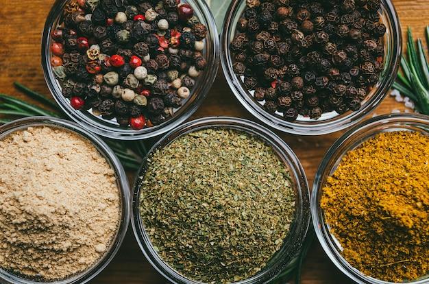 丸いガラスのボウルにさまざまなスパイス。生姜、ホップスネリ、カリ、黒コショウ、混合物。