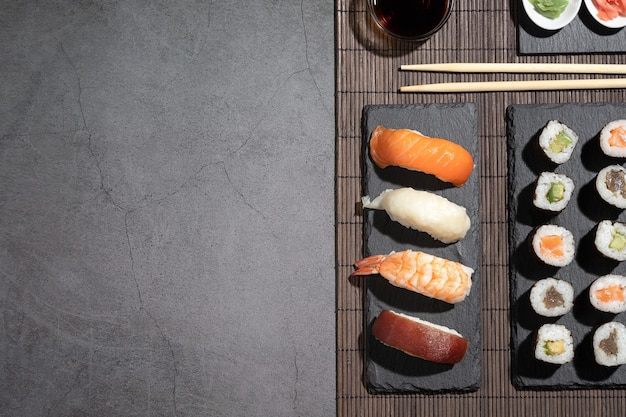 暗い背景にさまざまな寿司。コピースペース付き寿司セット。