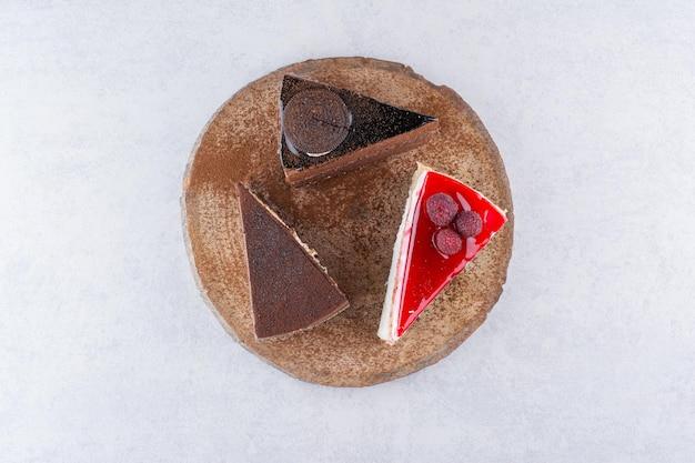 Разнообразие сладких пирожных на деревянном куске. фото высокого качества
