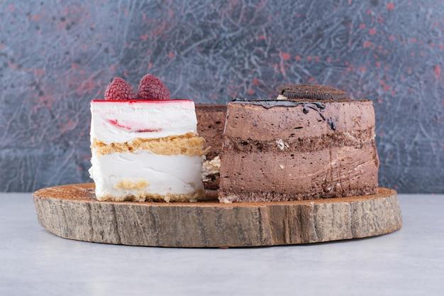 木片にさまざまな甘いケーキ。高品質の写真