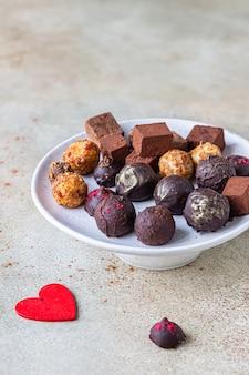 다양한 달콤한 수제 초콜릿 사탕과 트뤼플, 밝은 콘크리트 표면.