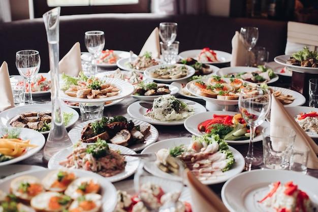 Разнообразие вкусных холодных закусок подается на белых керамических тарелках за столом для особых случаев свадебного банкета. ассортимент приготовленных закусок и еды на столе в ресторане. празднование рождества или нового года.
