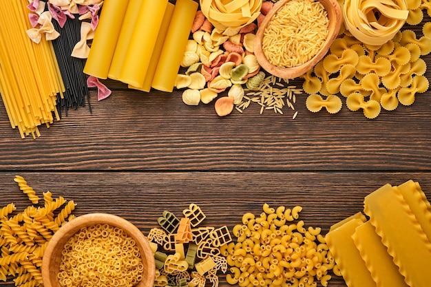 さまざまな伝統的なイタリアのパスタ: 古い木の背景にカラフルなスパゲッティ、タリアテッレ、ファルファッレ、ペンネ、プチット、ヌードル、フジッリ、カネロニ。コピー スペースのあるトップ ビュー。