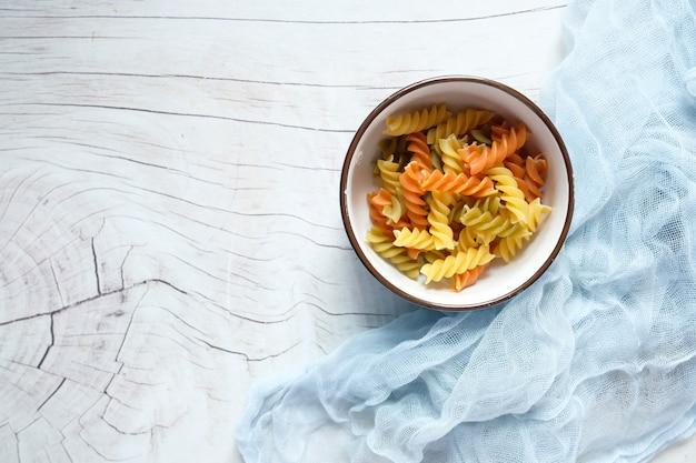 ボウルに入れる様々な種類と形の乾いたイタリアンパスタ。