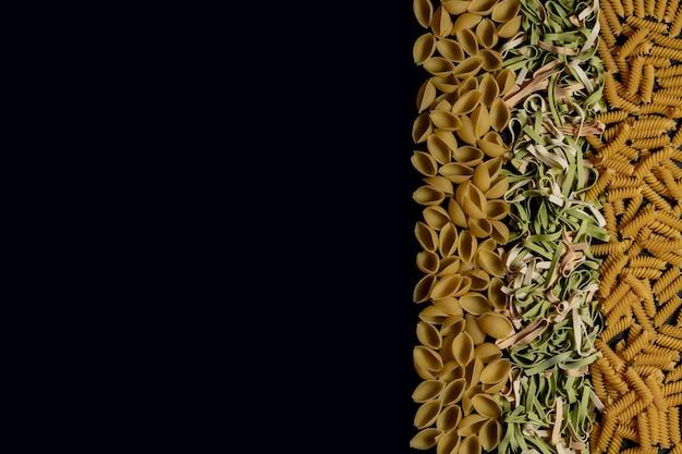 さまざまな種類と形の乾いたイタリアンパスタ。イタリアのマカロニローフード背景やテクスチャ:パスタ、スパゲッティ、スパイラルの形のパスタ。