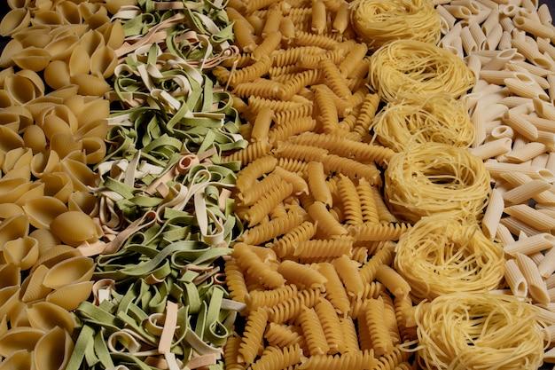 様々な種類と形の乾いたイタリアンパスタ。イタリアのマカロニローフード背景やテクスチャ:パスタ、スパゲッティ、スパイラルの形のパスタ。