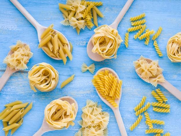 さまざまな種類と形の乾いたイタリアンパスタ。木製のスプーンと青色の背景にパスタの食材。上面図。フラット横たわっていた。