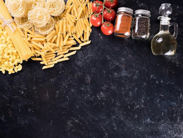 スパイス、フレッシュトマト、ひまわり油の横にあるさまざまな生パスタ。上面図。利用可能なコピースペース