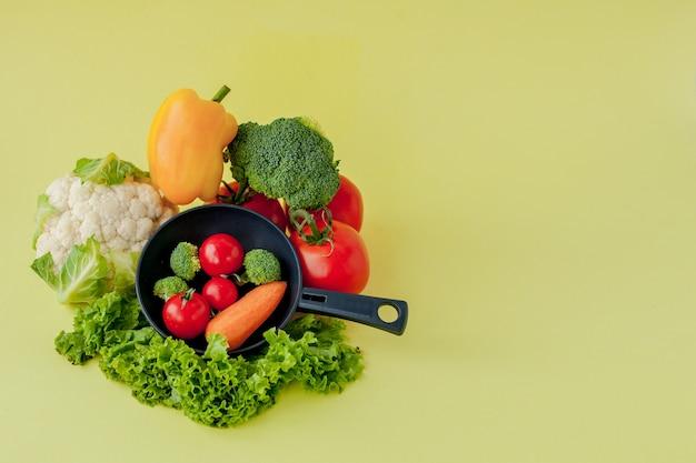 さまざまな野菜とフライパンを黒板に、上面図で表示します。ビーガンと健康的なコンセプト。