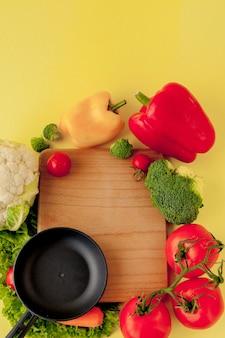 さまざまな野菜とフライパン、上面図。ビーガンと健康的なコンセプト。