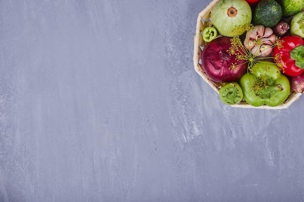 青いテーブルの上の竹かごの中のさまざまな野菜。